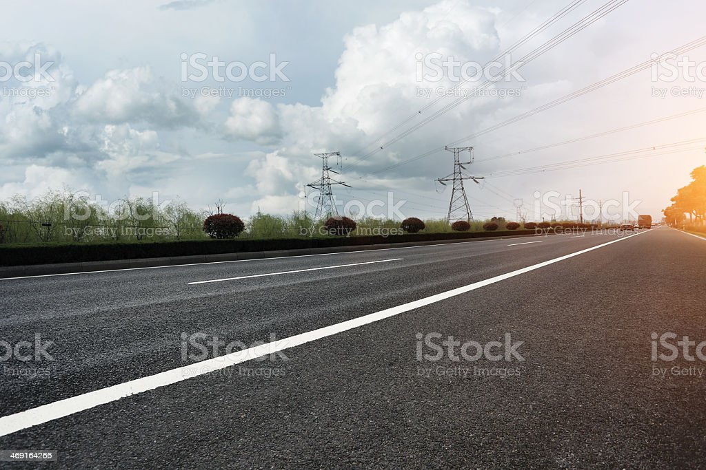 A view of a highway with electric power tower stock photo