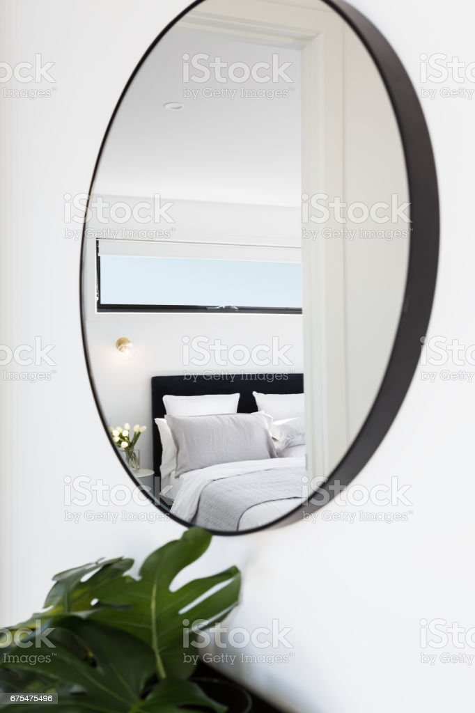 View of a luxury bedroom reflected in a hallway mirror stock photo
