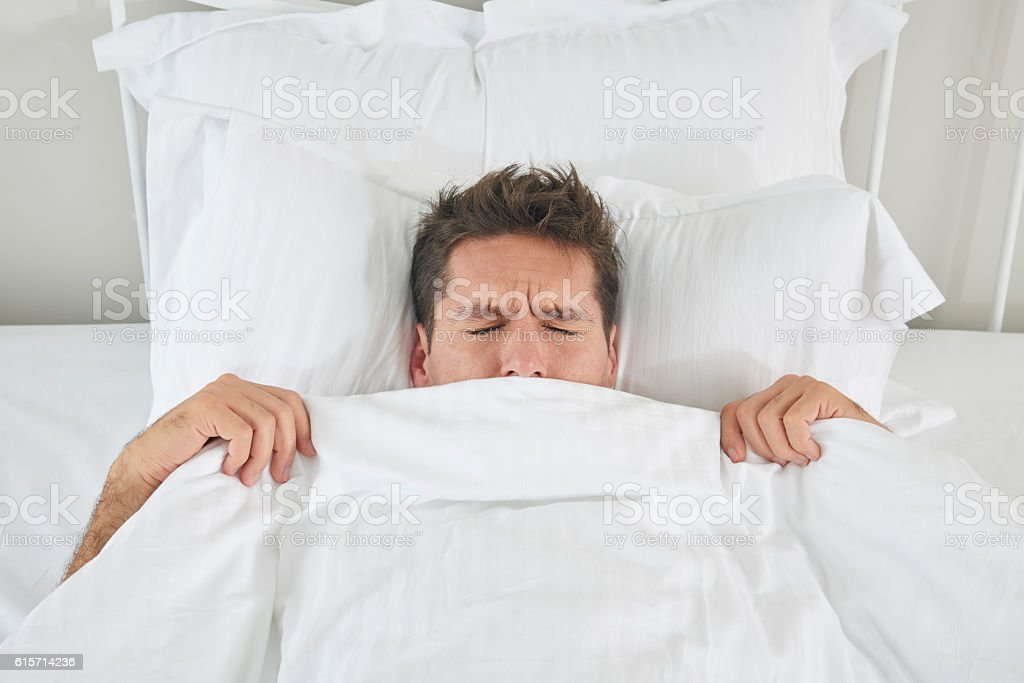 View of a man under the quilt stock photo