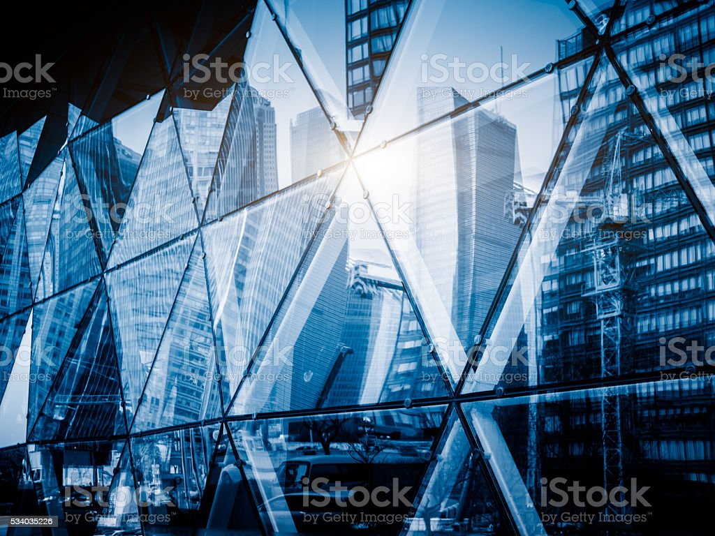 View of a modern glass skyscraper reflecting the blue sky stock photo
