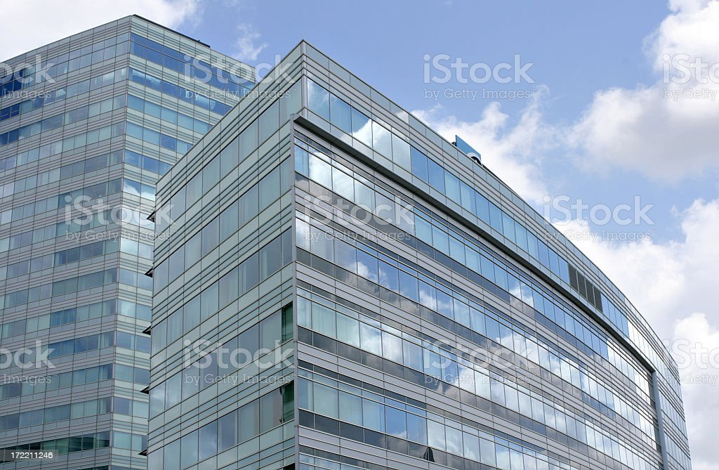 A view of a modern office building with clouds reflecting royalty-free stock photo