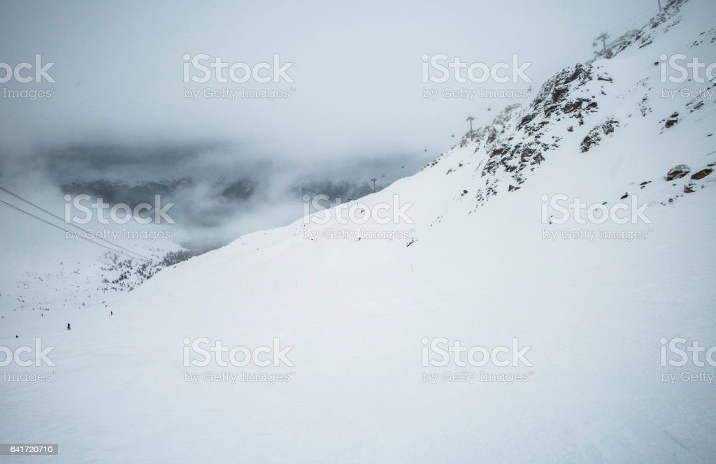 View of a ski slope in cloudy mountains stock photo
