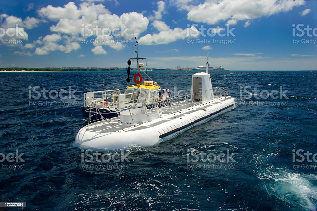 View of a submarine on top of water with blue sky and clouds stock photo