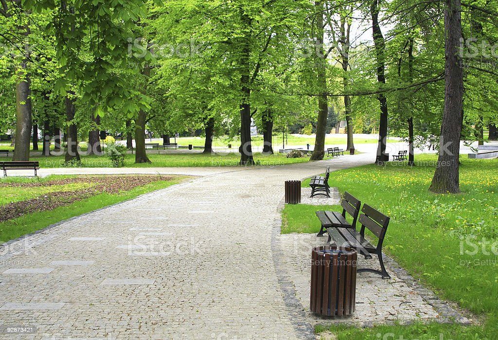 View of a walkway in a green park stock photo