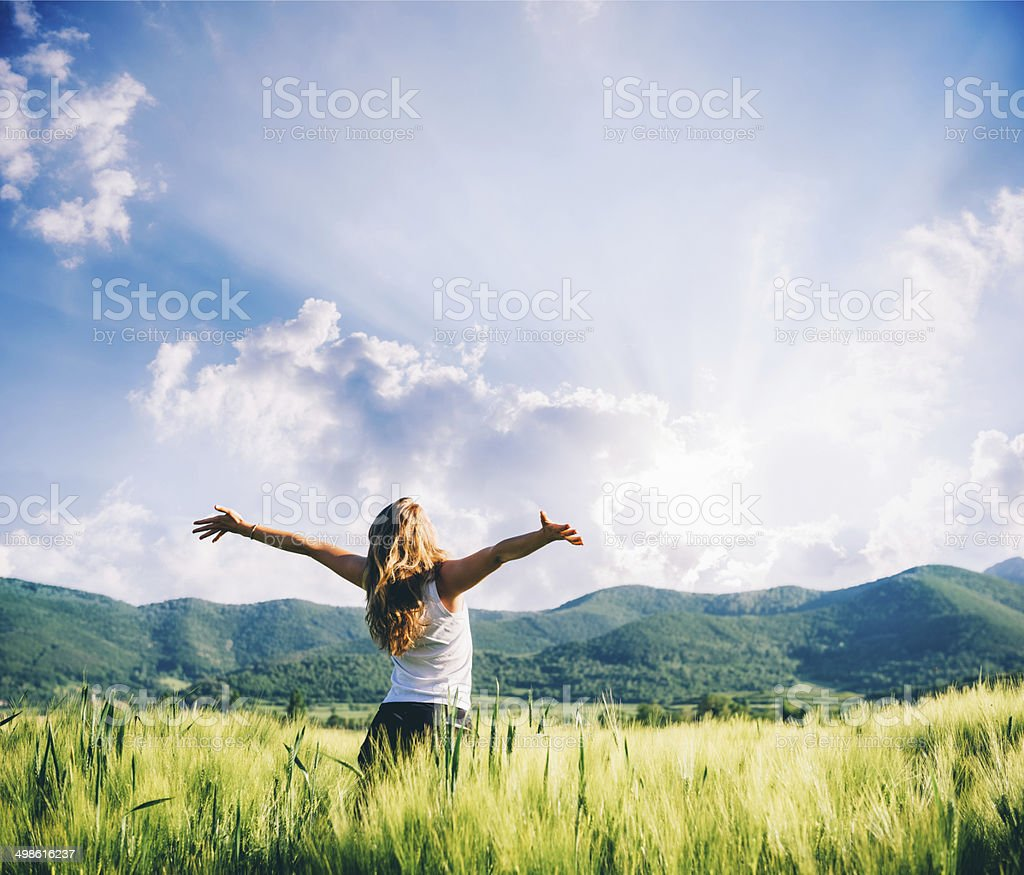 view of a woman in the wheat field beeing happy stock photo