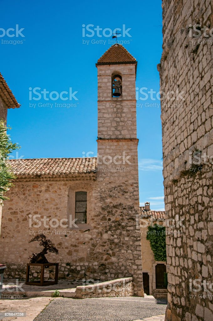 View of alley and church with stone steeple tower in Saint-Paul-de-Vence. stock photo