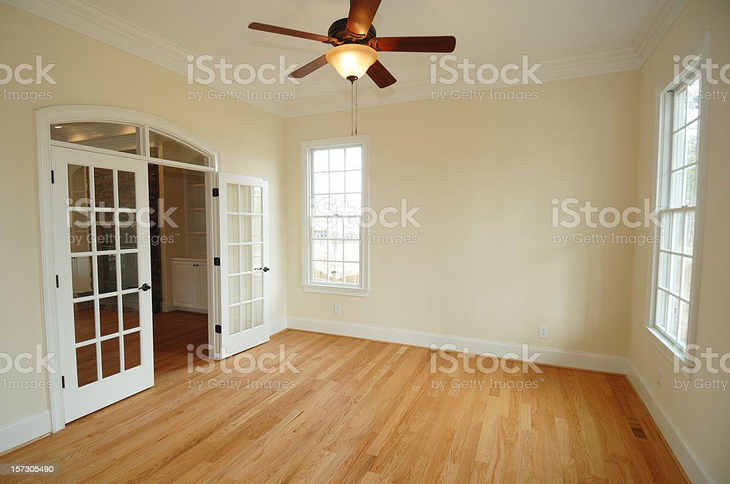View of an empty room showing a roof fan and open door royalty-free stock photo