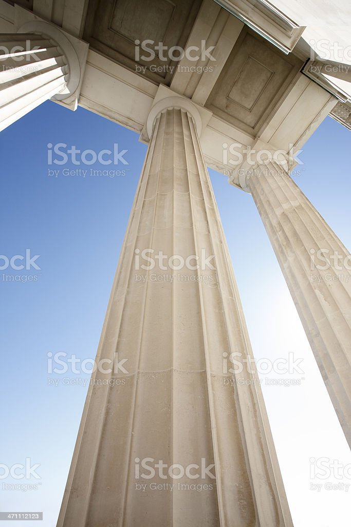 View of architectural pillars against blue sky stock photo