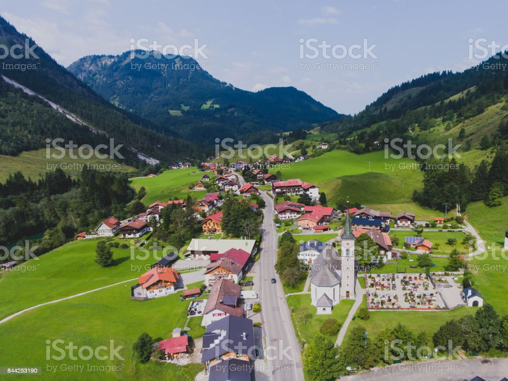 View of bavarian alpine village with a valley and mountains, shot from drone, Bayern, Bavaria, Germany, sunny summer day stock photo