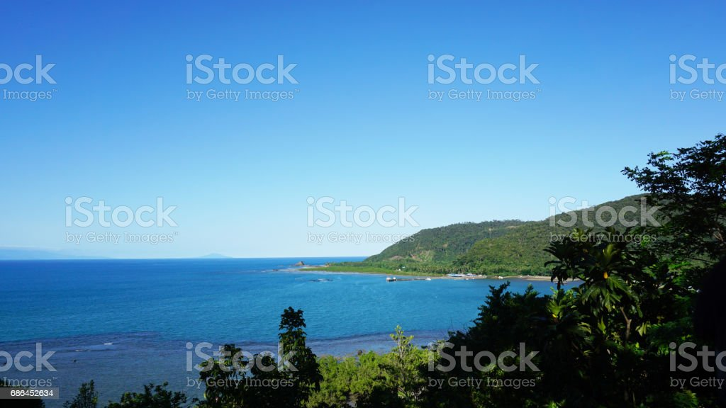 View of beautiful blue sea and clear sky from afar with mountain and trees stock photo