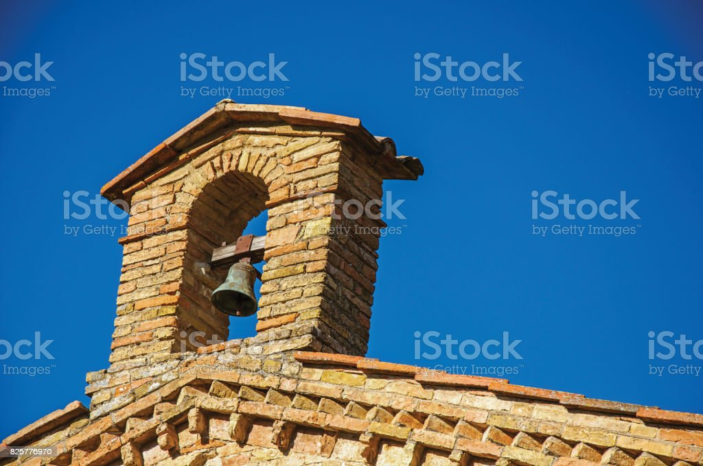 View of bell on top of brick church and blue sunny sky at San Gimignano. stock photo