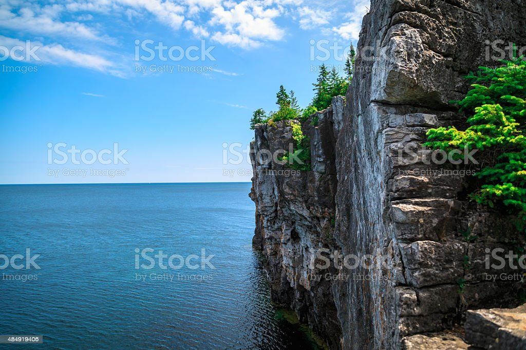 View of big long rocky cliff standing in lake Huron stock photo