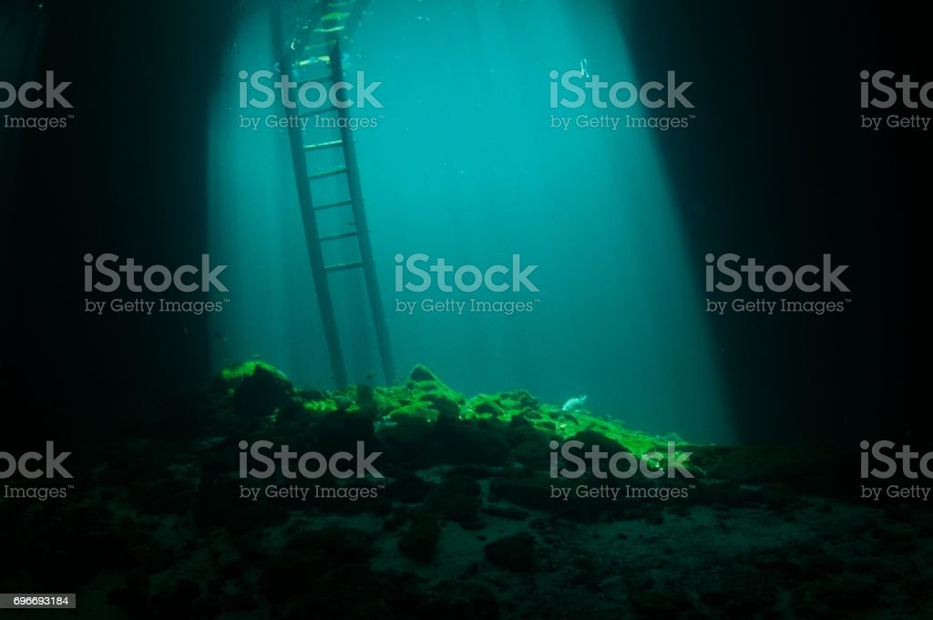 view of blue laser beams coming down around ladder at entrance to cenotes with darkness around stock photo