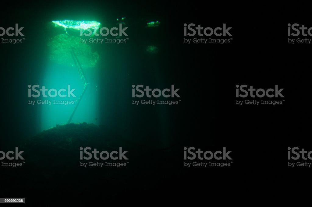 view of blue laser beams coming down around ladder at entrance to cenotes with darkness around 2 stock photo