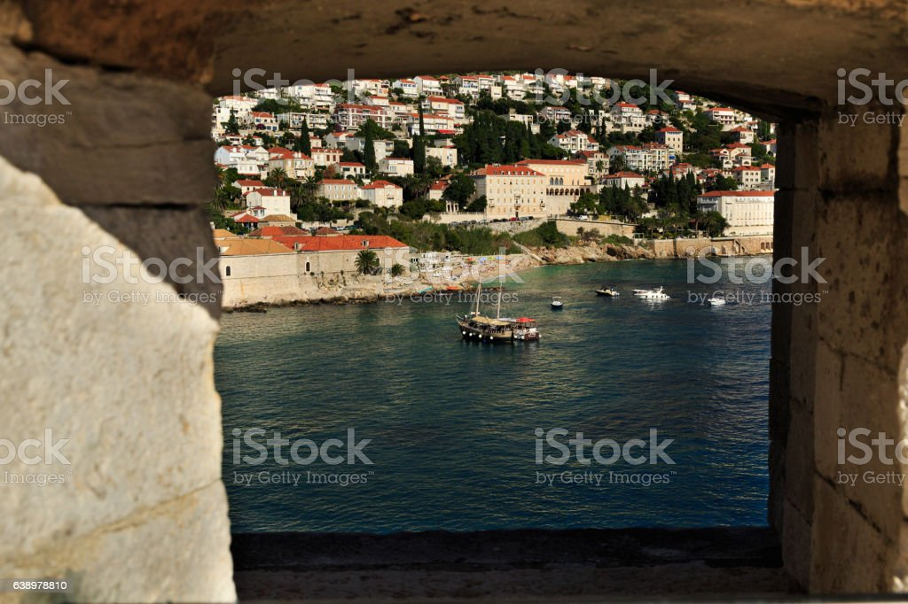 view of boats and modern Dubrovnik through a loophole stock photo