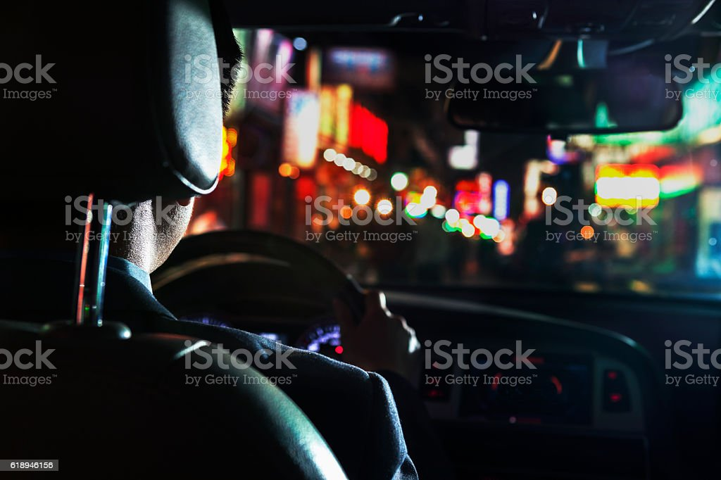 View of businessman driving car at night stock photo