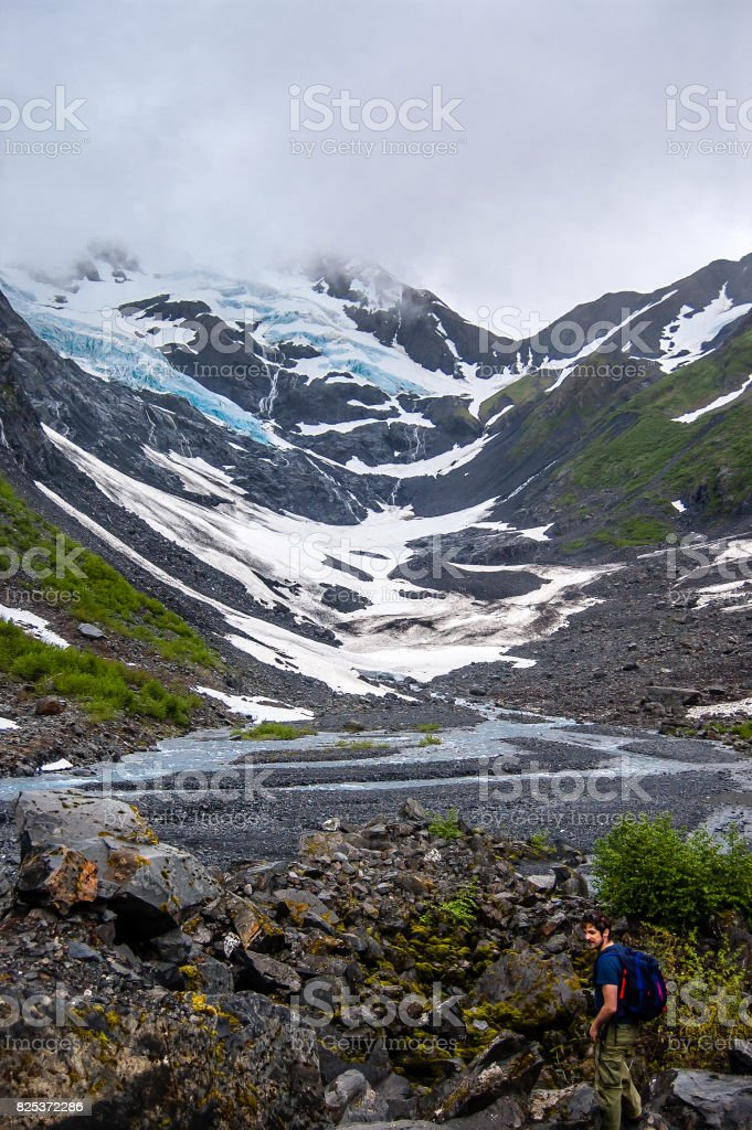 View of Byron glacier and a tourist hiking stock photo