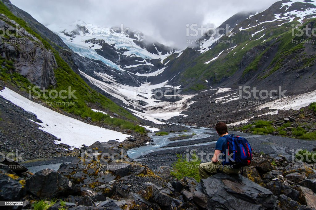 View of Byron Glacier and Byron creek and a tourist admiring the view stock photo