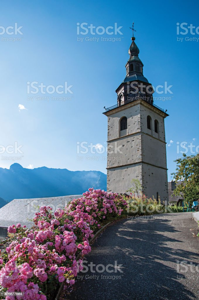 View of church steeple and flowers in the medieval village of Conflates. stock photo