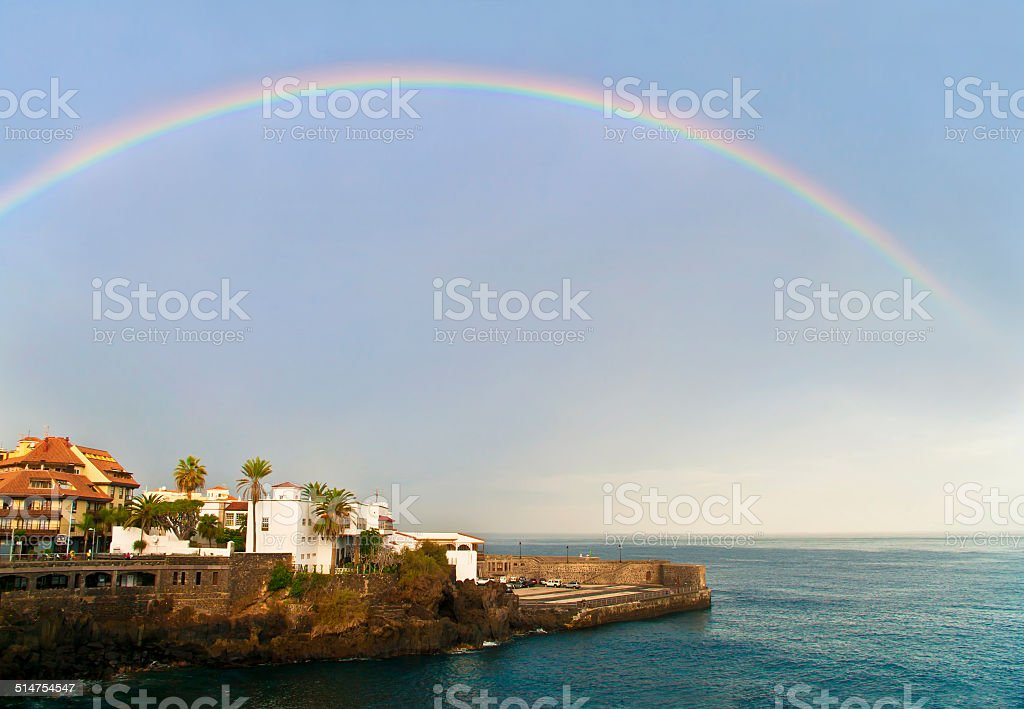 view of city by seaside and rainbow stock photo