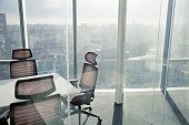 View of city with sunlight through window in meeting room