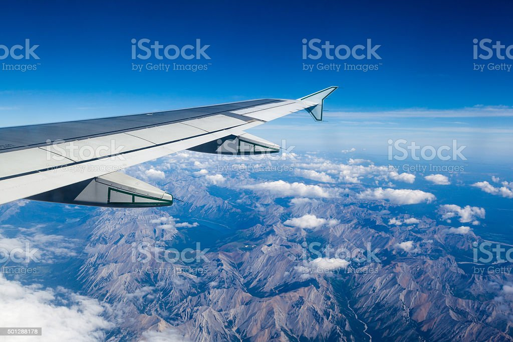 View of clouds and Rocky Mountains outside airplane window stock photo