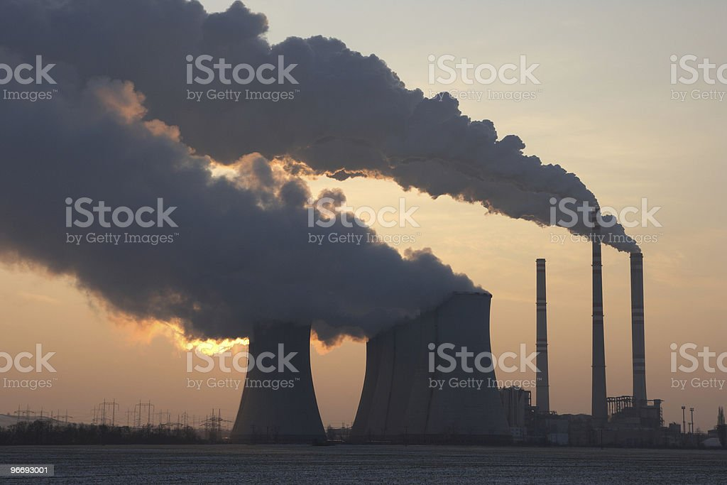 View of coal power plant against sun and huge fumes stock photo