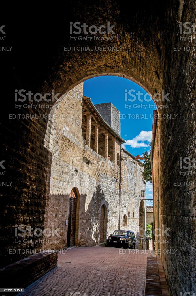 View of dark alleyway, brick building and tower in San Gimignano stock photo