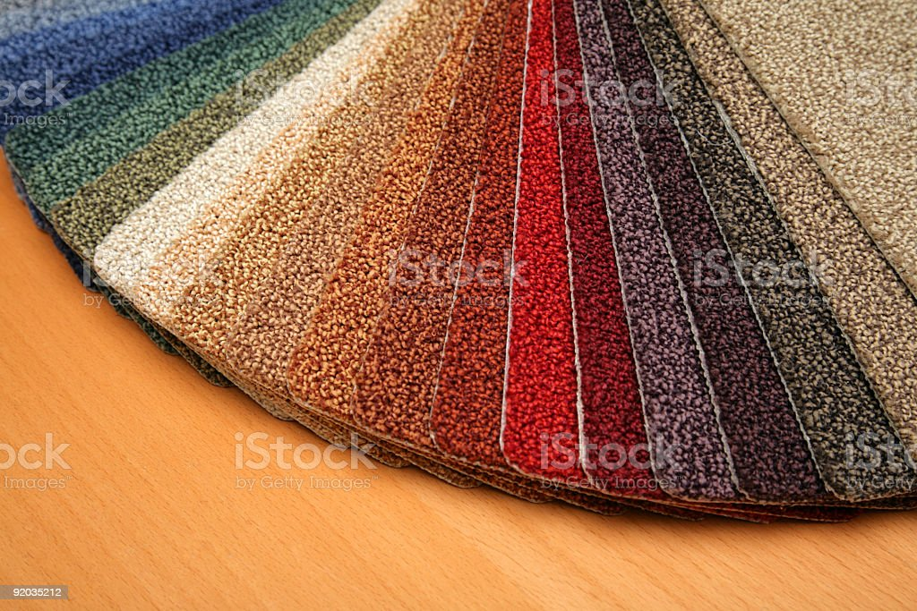 View of different types of carpets on a wood floor stock photo