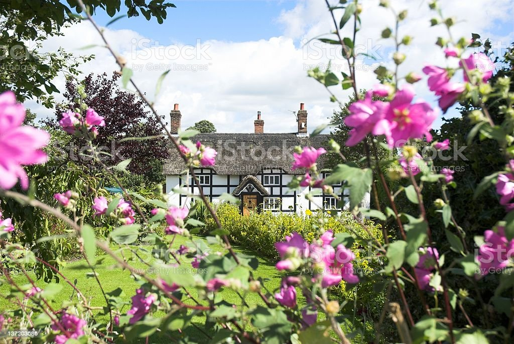 View of English Cottage through the garden flowers stock photo