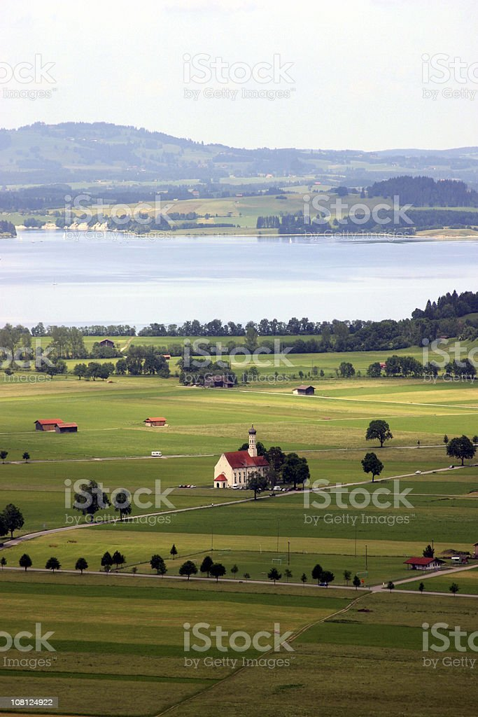 View of European Countryside with Farms, Lake, Chuch and Houses royalty-free stock photo