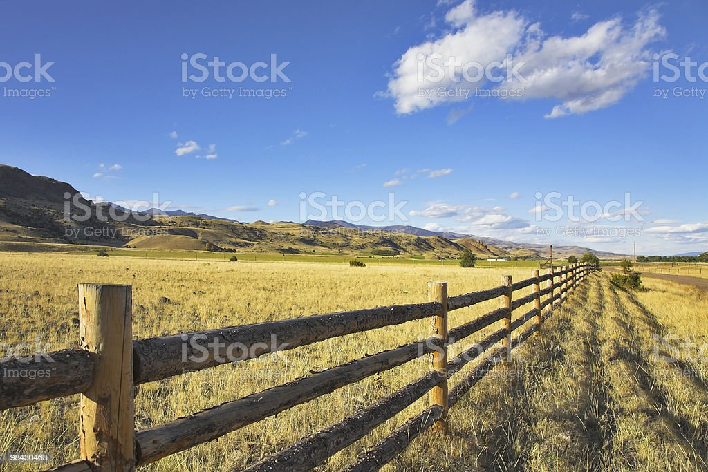 View of fence to horizon in farm field and blue sky royalty-free stock photo