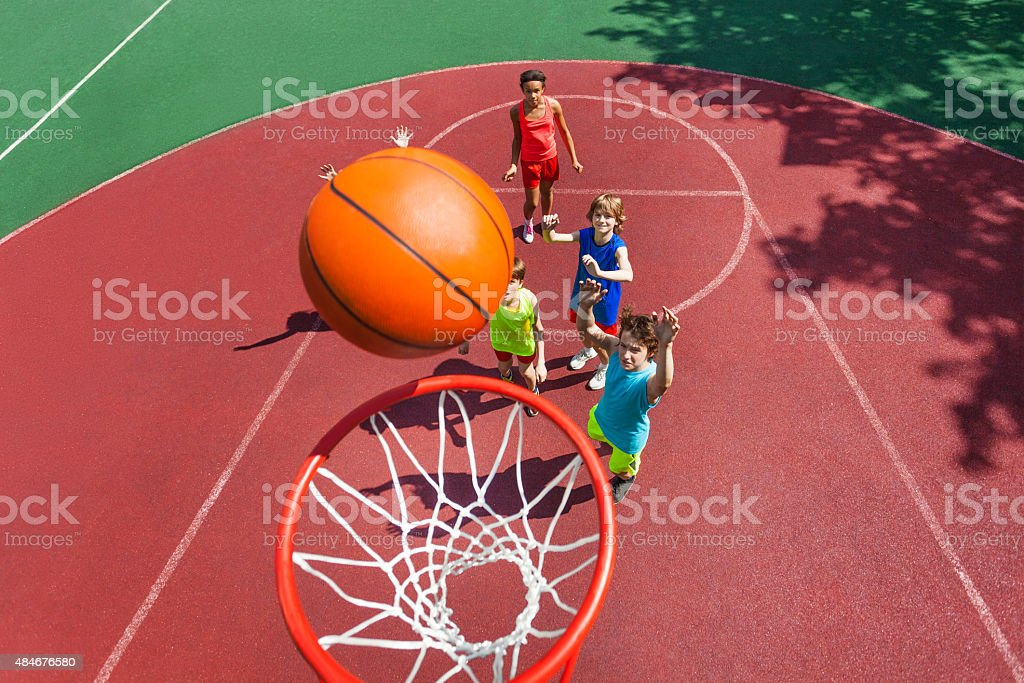View of flying ball to basket from top, teens play stock photo