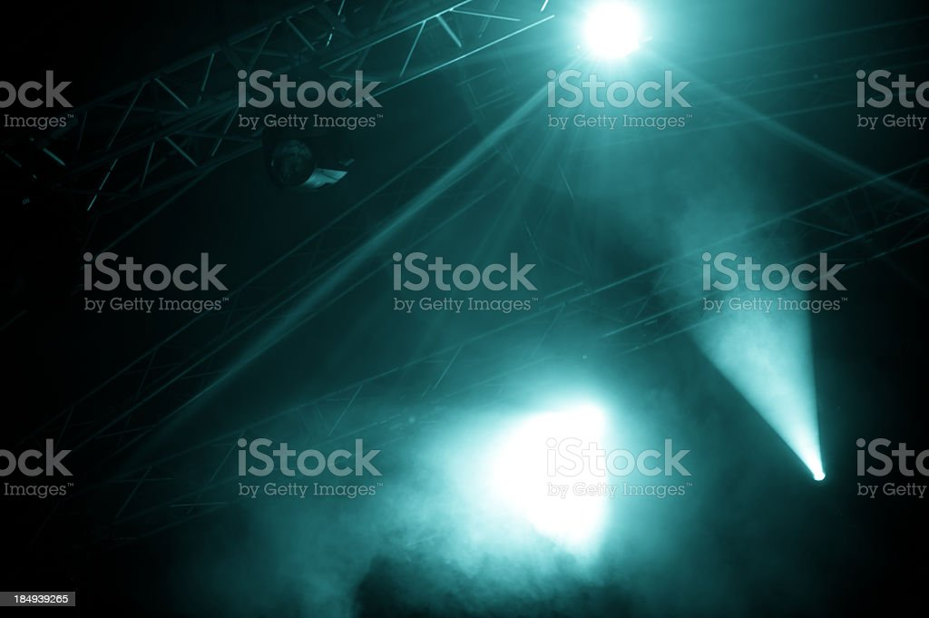 A view of foggy stage lights emerging from the dark stock photo
