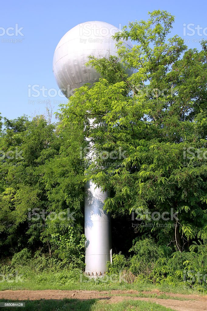 View of globular water tower at village farm between trees stock photo