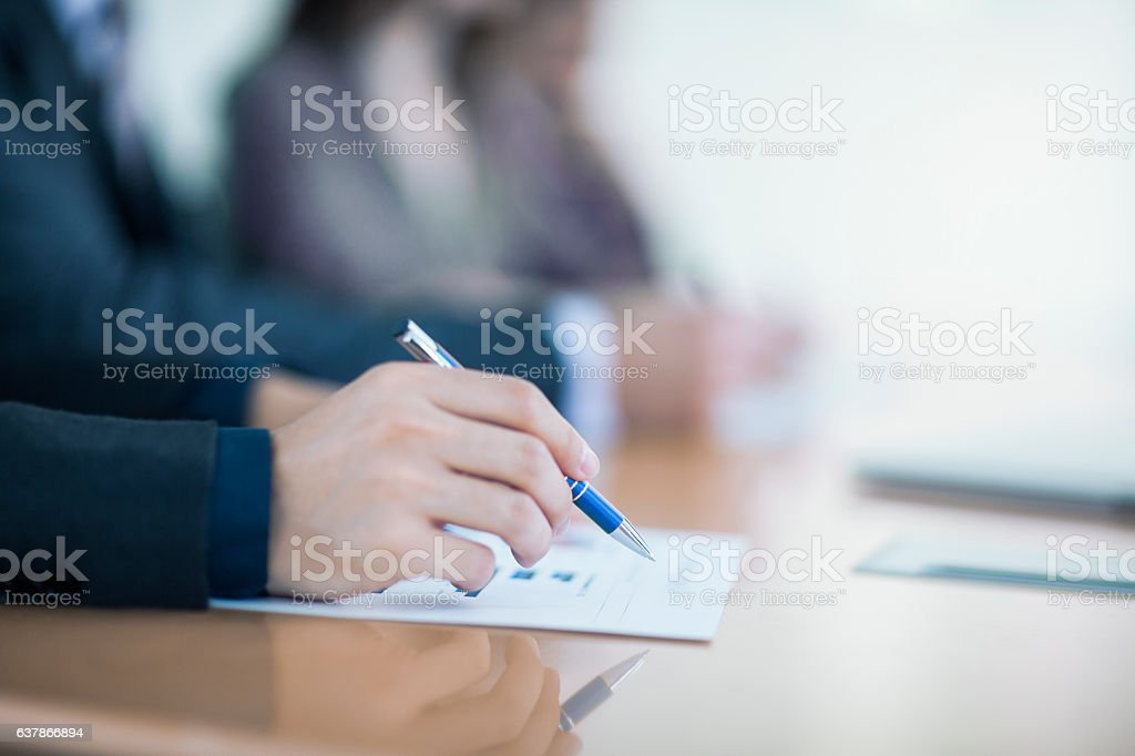 View of hand writing on document in business meeting stock photo