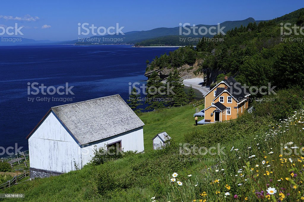 View of house and barn on hill by water royalty-free stock photo