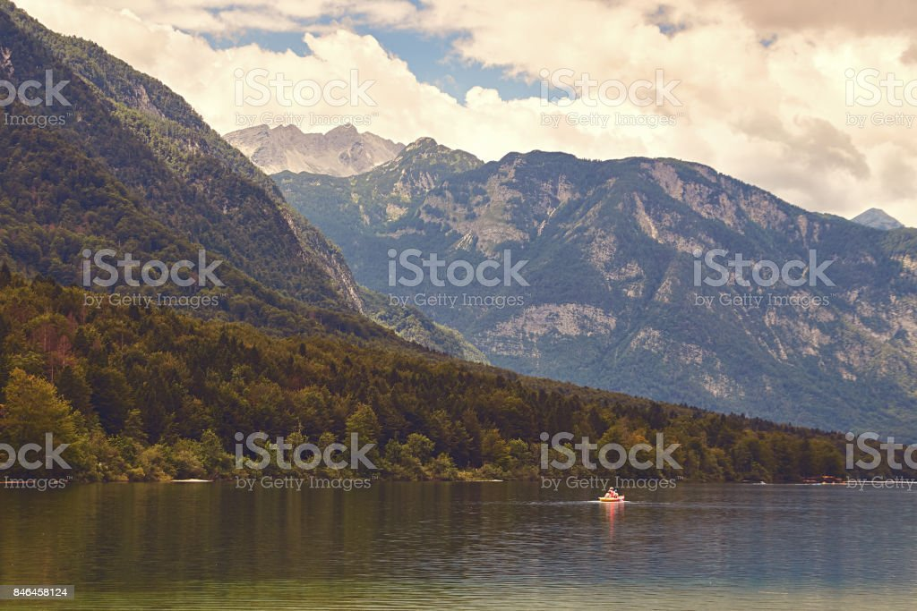 View of lake Bohinj with the boat sailing across it stock photo