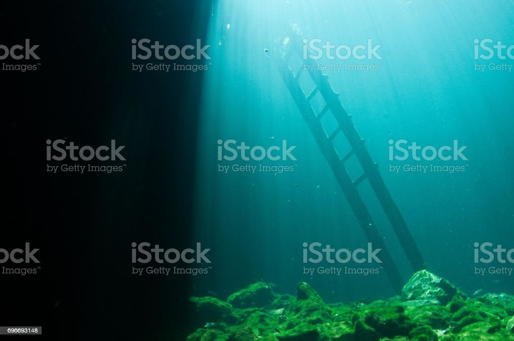 view of laser beams of blue light by entrance and ladder at cenotes 1 stock photo