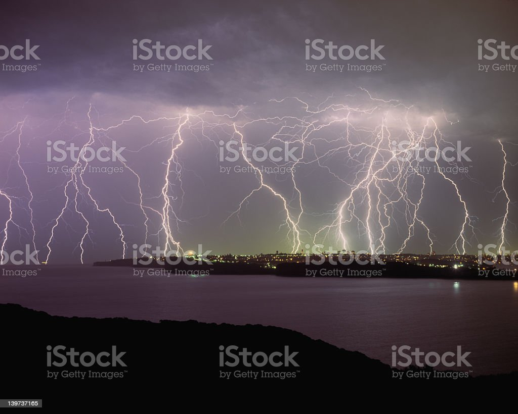 View of lightening striking a city from across a river stock photo
