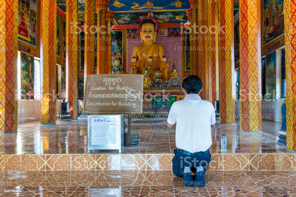 View of man in prayer in front of Buddha, Cambodia stock photo