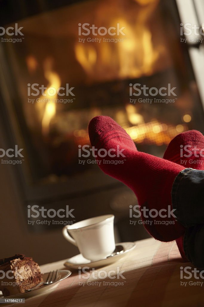 View of man's red socked feet with coffee cup by a log fire stock photo