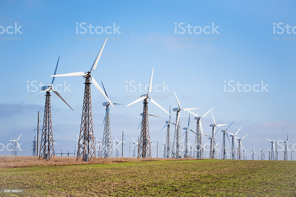 View of many wind turbines on blue sky background. stock photo