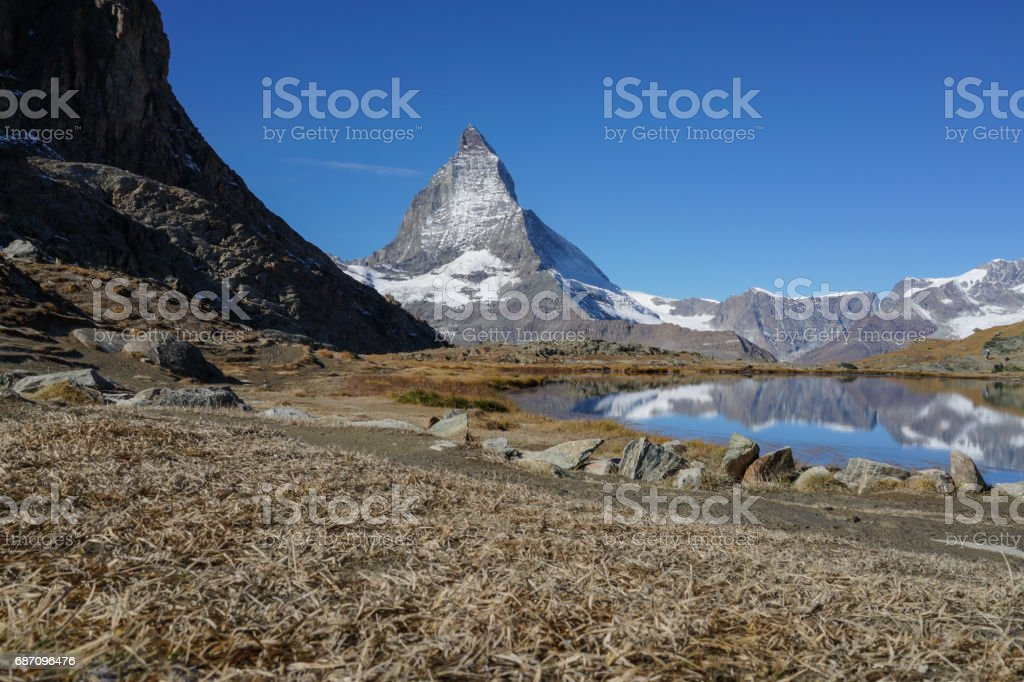 View of Matterhorn mountain with dried glass and lake foreground with clear blue sky in autumn, Switzerland. stock photo