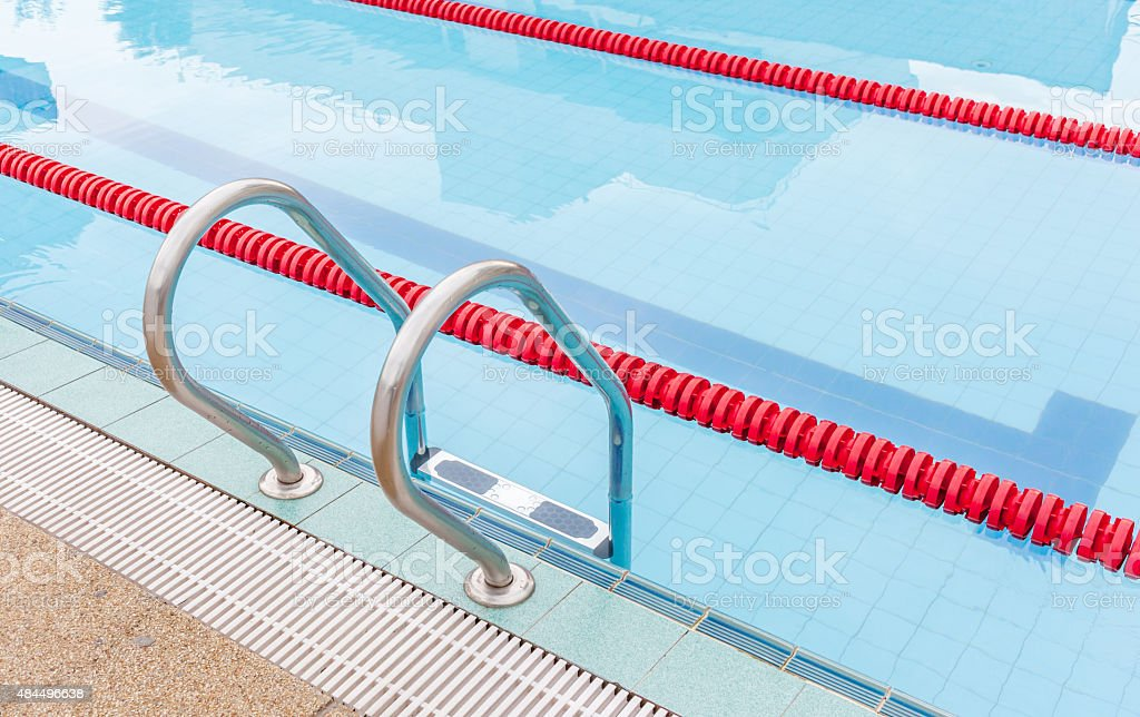 View of metallic ladder of swimming pool with marked lanes. stock photo