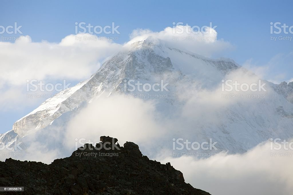 view of mount cho oyu in the middle of clouds stock photo