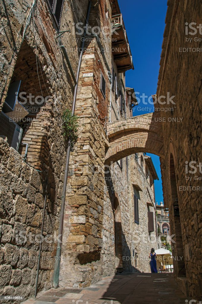View of narrow alley with old buildings, arch and woman walking in San Gimignano stock photo
