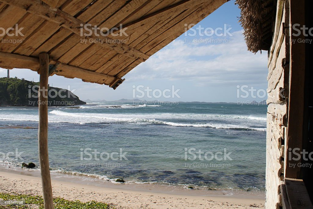 VIew of ocean from a wooden beach shack awning stock photo
