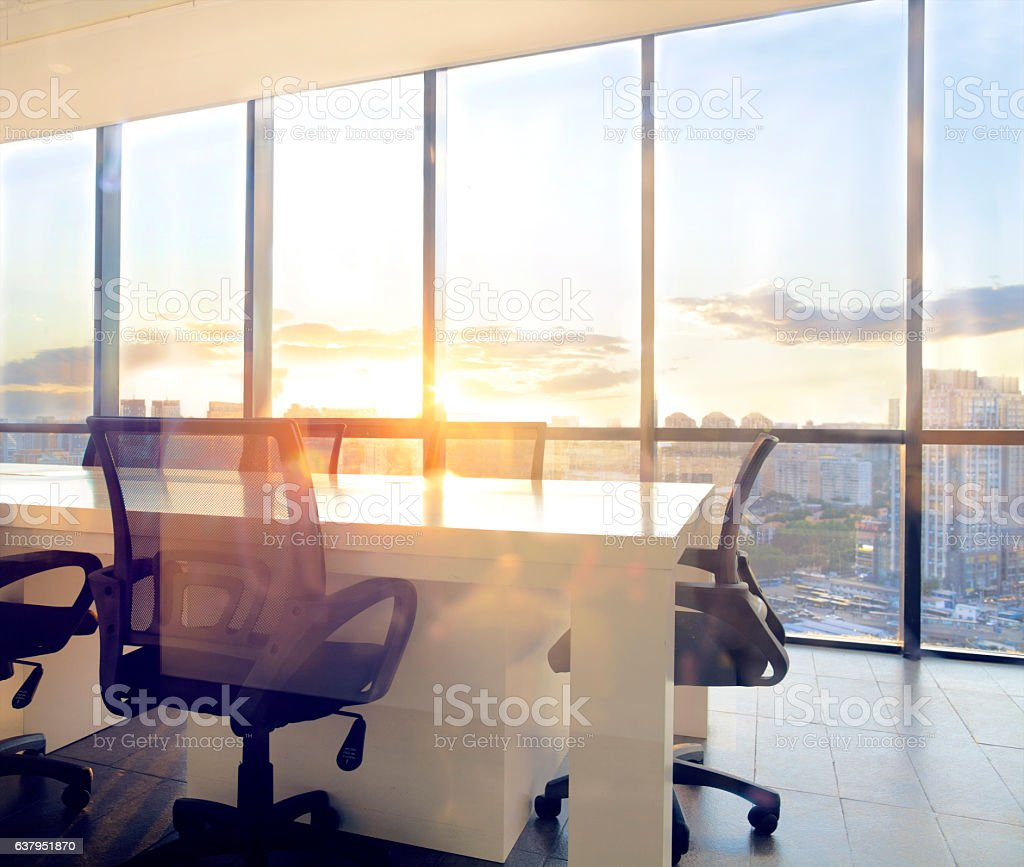 View of office conference room with sunset light in windows stock photo