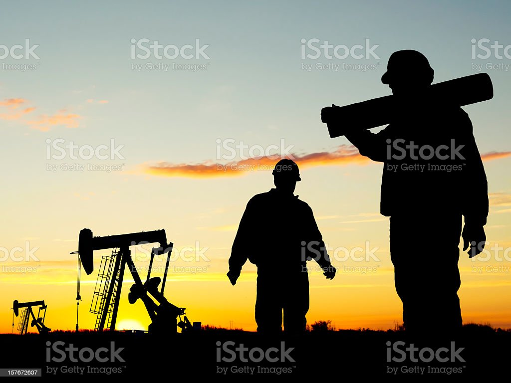 A view of oil workers at Well Pumpjack Site at dusk  royalty-free stock photo